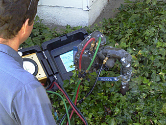 San Marcos sprinkler repair technician examines a backflow prevention device
