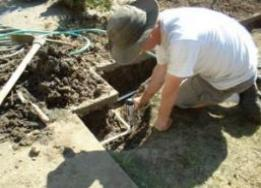 Irrigation repair contractor works on a valve box